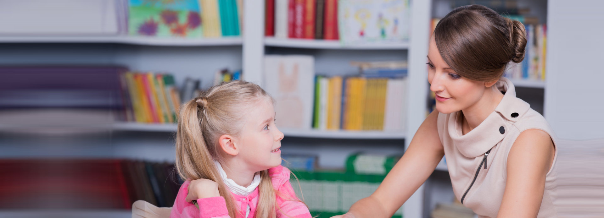 beautiful psychologist having a therapy session with little girl