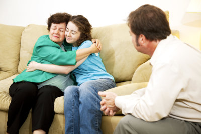mother and daughter hug to each other while having a therapy session